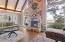 The great room features a floor to ceiling stone fireplace with pecky cypress walls, a beamed ship lap ceiling, and a spiral staircase to the loft above.