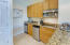 Kitchen with granite counters, tile flooring and stainless appliances.