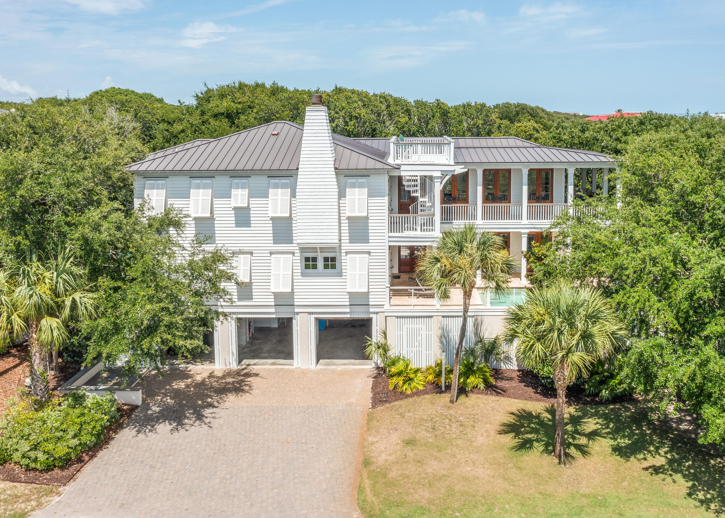 Incredible second row hidden gem on Isle of Palms! This premier custom home by Sheppard Construction features everything you need for island living on a grand scale and only steps from the beach! This beautiful home is one of the best on the island; second row for easy access to the beach, elevated pool and deck, privacy provided by mature Live Oaks and other greenery, custom kitchen, and an open floor plan with multiple gathering spaces with doors and windows designed to catch the ocean breezes and beautiful natural light all day. After a walk on the beach, cool off in the pool, enjoy a meal made in the custom kitchen, or just relax on one of the many porches.  Conveniently located close to dining, shopping, and outdoor activities on the island and in nearby Mt Pleasant and Charleston. The custom chef's kitchen features a SubZero refrigerator, Wolf six burner range with double ovens, marble countertops, custom cabinetry, ice maker, wine fridge, and a large island with seating for four.  The second floor is rounded out with a main living area with fireplace, second seating area, dining area, two bedroom suites, and access to the full length porch and spiral staircase to the rooftop deck.  On the first floor, you will find a media/living room and spacious main bedroom suite with direct access to the pool deck, and three more bedrooms and two bathrooms.  3301 Palm's other features include beadboard paneling, oak hardwood flooring throughout, central vacuum, and an elevator for your convenience..Designed with island life in mind, this well equipped home is the quintessential Isle of Palms beach house.Currently on a vacation rental program - rental numbers available upon request.