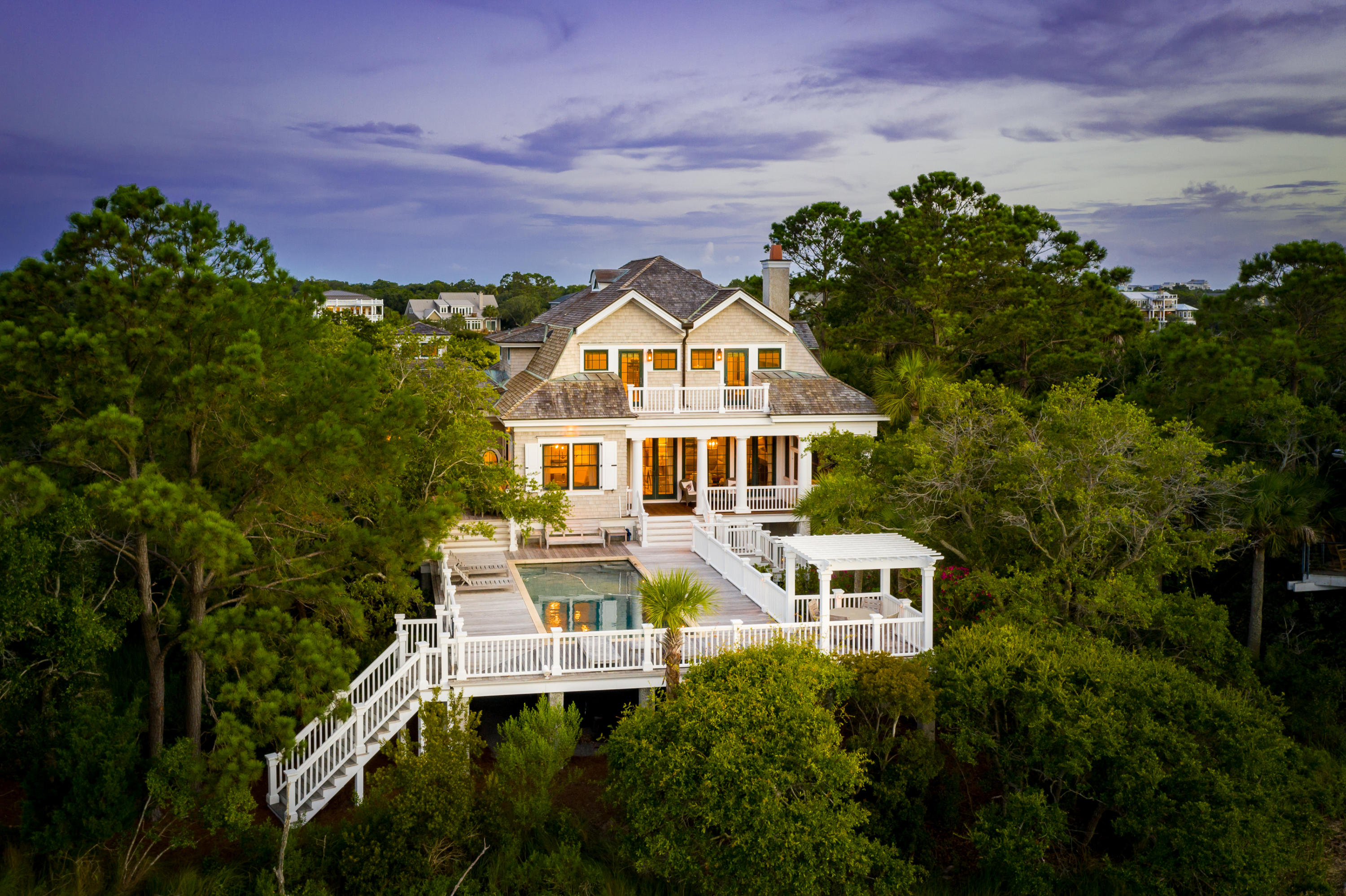 Masterfully designed by Christopher Rose, and built to the highest standard by Philip Smith, this luxury Lowcountry retreat offers a level of privacy and serenity rarely found on Isle of Palms. Nestled among the Palmettos, this Cape Cod style home welcomes all with beautiful shake exterior and off-centered front doorway. The property spans 2-acres, boasting its own tidal lagoon, elevated back deck, saltwater pool and truly gorgeous long-marsh views towards the Intracoastal Waterway. As showcased in American Dream Homes Magazine, the residence is truly one to behold, with no detail neglected through its design and construction - a true luxury coastal estate. As you enter the home, two separate studies bookend the powder room and oversized foyer. The entry space features a prominent  turning staircase and first glimpse of detailed wainscoting and crown molding as seen throughout. Soft natural light floods the space through the surrounding Carolina tree line and carefully designed eyebrow-style skylights from the upper floor. The light is met by accented white walls and cherry hardwood floors which connect most of the interior. As you are invited in through the foyer, you are met with an amazing great room. Here, French doors line the exterior, allowing owners and guests to view the beautiful, vast saltwater marsh from the comfort of the home. To the left, the coiffeur ceiling and stone fireplace promote a warm setting perfect for gathering with family and friends. To the right, dining and kitchen spaces flow together perfectly in an open setting. Ro Sham Beaux and Circa lighting fixtures hang overhead and compliment the marble counters and stainless-steel appliances. The gas range, peninsula bar and large kitchen island make this space perfect for cooking, and entertaining is made easy through built in smart-home and Sonos surround-sound systems. A wet bar is placed just outside the great room, with wine cooler and storage. The main floor guest bedroom sits to the lef
