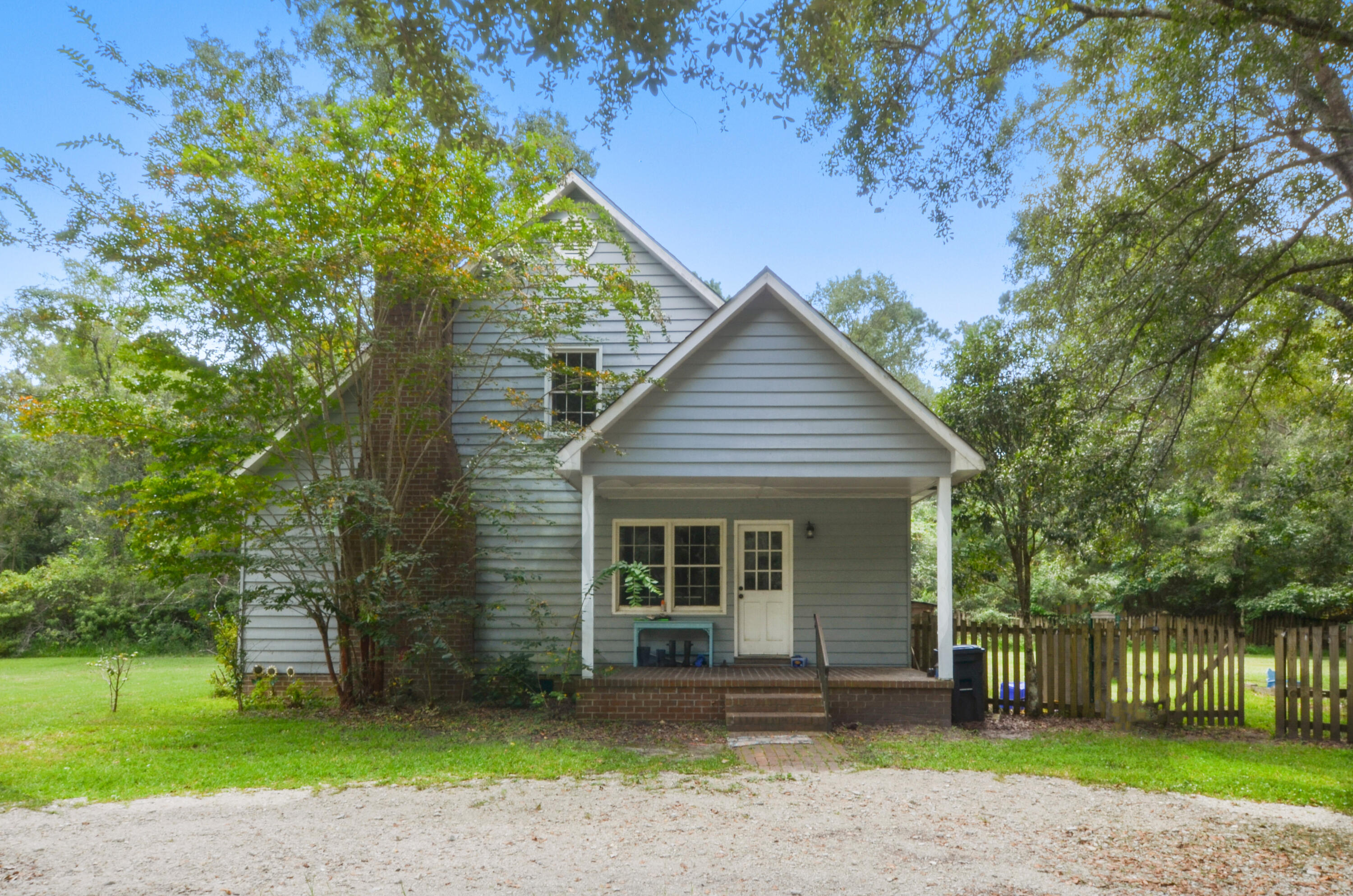 Set in the middle of a 3-acre tract, this lovely 4 bedroom, 2.5 bathroom home offers privacy while still having easy access to everything. CREECS charter school is literally right across the road and the restaurants and boat landing are all with a couple of miles. There is a fenced-in back yard and large garage/workshop. The home is on a small crawlspace with just a few steps up to the covered porch and qualifies as above flood code for lower insurance rates. The home has hardwoods throughout. You enter into the kitchen with a room for a 4-person dinette. To your left is one of the home's living areas which includes a fireplace and large window. Next is a dining room with built-in cabinets with glass doors to display your china. Beyond the dining room is the second living area with an exterior door and stairs leading to the upstairs. Around the corner is the downstairs master bedroom with dual closets. From the kitchen, you can also go straight down the hallway which includes a pantry, laundry room with back door to fenced yard, half bath, two storage closets, and ends at the master bedroom.  Upstairs are two very large bedrooms with dual closets and dormer windows. The third upstairs bedroom is average size and includes a closet but could also make a great office or workout room with a view out to the backyard. The layout of the home could be changed such that you enter into the second living area if you modified the driveway.   In 2018, both HVAC units and all of the ductwork was replaced with top-of-the-line Trane systems and wi-fi enabled thermostats. Under the home was also encapsulated and additional supports were installed by a licensed professional to repair rolling floors. The pantry and upstairs bathroom were also recently renovated.   Home inspection furnished upon request. Listing price reflects repairs needed and home is being sold as-is. Owner is agent/broker.