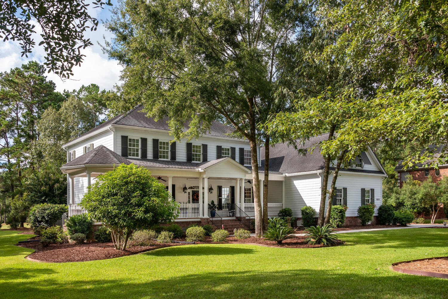 Stunning custom built lowcountry style home featuring an inviting wrap-around porch and situated on a beautifully landscaped 1 acre golf course lot. Walking through the front door the welcoming foyer is flanked by a formal living room on the left flowing seamlessly into the family room and a formal dining room on the right with direct access to the kitchen. The family room showcases a hand carved mahogany mantle, stately built in bookcases and french doors that lead to an oversized screened porch and patio with endless views of the retention pond and golf course beyond. The custom kitchen open to the family room does not disappoint, featuring rich cherry bordeaux pull-out drawer cabinetry, double ovens, a center island and large pantry. The downstairs master bedroom. overlooks the golf course and allows access to the screened porch. The well appointed recently renovated master bathroom includes a jetted hot tub, separate shower, dual vanities and a large walk in closet.  A spacious laundry room is conveniently located adjacent to the master bedroom on this level. The second floor is accessible by two separate flights of stairs one of which is located in the foyer and the other at the back of the home off of the kitchen. The second floor features an oversized media room as well as an additional game/fitness room.   Three additional guest rooms including a second master bedroom with a large master bathroom and oversized closet complete this level. The third floor walk up attic offers plenty of storage and endless possibilities of being finished off as an additional bedroom if needed. The three car garage features epoxied floors and ample storage space. Additional features of this home include a Rinnai tankless hot water heater, custom hurricane shutters and a central vacuum system throughout the entire house. Buyers will love the privacy that this beautiful executive home offers on one of the most desirable streets in Dunes West.