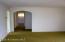 Living room has wood floor underneath the carpeting.