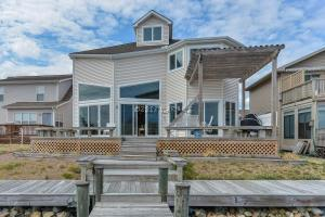 NO CITY TAXES! Luxury Coastal Contemporary Bayside Waterfront Living at 13461 Madison Ave. North Ocean City. This Custom Built High Quality Construction Home was Built as a Builders' Personal Residence with panoramic water views and private dock with boat lift. Plenty of natural light flows throughout the home's open, airy layout. Generously-sized living/dining area with gas fireplace for family gatherings graced by huge windows and glass sliding doors that lead out to the rear decks. The sprawling entertaining spaces flow outside to the multi-level sun decks and tranquil premier bay front. First-floor MASTER suite offers built in dressing table and en-suite tile bath with soaking tub. Upstairs has guest rooms with private bath plus huge 3rd floor bonus room with OC skyline views!