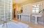 Dual pedestal sinks, built in cabinetry, bathtub, glass block & surround shower.