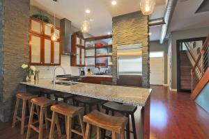 Awesome eat in kitchen with open shelving & custom stone wall.