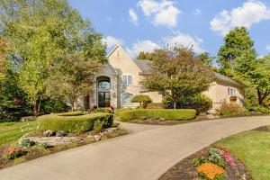 Gorgeous stone and stucco home with a circular drive.