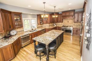 "KITCHEN features hardwood flooring, 42"" cabinets w/under-lighting & lighted display, granite counters, center island w/breakfast bar, built-in planning desk/buffet area . . ."