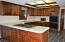 Chef's kitchen features large eating area, an abundance of beautiful cabinets and counter space, and large walk-in pantry.