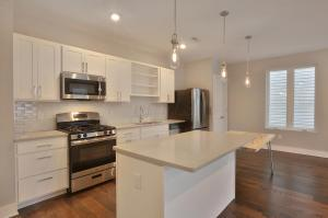 White soft close cabinets, grey quartz counters, french door refrigerator, gas range, pendant lights and more