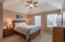 Large master bedroom with vaulted ceilings and ceiling fan/light combo.