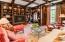 Walnut flooring, coffered ceiling, custom leaded glass French doors, custom TV cabinet behind shield, bookshelves, desk and drawers.