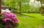 The home is surrounded by flowering trees and perennials.