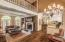 Crown molding, exposed brick, built-in cabinetry and shelving, wood paneled wall with track lighting and chandelier.