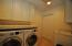 Laundry room has plenty of storage, folding table, sink, and additional closet space.