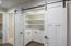 Walk-in pantry with custom cabinets.