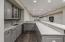 Updated bar area with quartz countertops and ceramic backsplash.