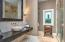 • Heated travertine flooring • Taupe textured papered walls • Enclosed vanity with single bowl, stone sinktop • Framed mirror • Lighted wall sconces • Linen closet • Shower stall w/ith glass enclosure and tumbled marble surround • Ceiling exhaust