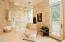 • Tumbled marble surround • Rain head • Dual shower heads • Glass doors • Speakers