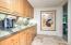 • Heated travertine flooring • Enclosed vanity with single bowl, stainless steel countertops • KitchenAid® microwave • SubZero® refrigerator