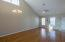 Spacious vaulted living room with hardwood floors, ceiling fan and neutral paint!