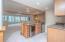 • Ceramic tile flooring • Tan painted walls • Granite countertops • Beverage center • General Electric® refrigerator • Single bowl, stainless steel sink • Wall cabinets • Pendant lighting