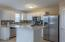 Eat-in kitchen with white cabinets, tile backsplash, ceramic tile flooring, stainless steel appliances and walk-in pantry!