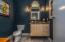 • Ceramic tile flooring • Grey painted walls • Crown molding • Can lighting • Enclosed vanity with single bowl, concrete sinktop • Lighted wall sconces • Mirror remains