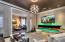 • Hardwood flooring • Grass cloth papered walls • Crown molding • Can lighting • Hanging chandelier • Glass wall separator • Drapes remain • 10 ft glass fireplace • Sound bar • TV remains