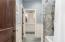 Convenient Pocket Door Provides Privacy. Wainscoting - Ceramic Tile Flooring - Tile Surround