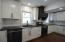 Two-tone leather finish granite counter tops with white cabinetry and black vent hood for a dramatic touch.