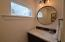 Half bath features furniture-style vanity, hex tile flooring, and gorgeous lighting selections.