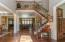 Hardwood flooring, taupe painted walls, two story ceiling, hanging chandelier, (2) coat closets