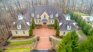 IMPRESSIVE! STONE & BRICK ENGLISH COUNTRY DESIGNED HOME WITH ~10,000SF ON NEARLY 3 PRIVATE WOODED ACRES W/ STREAM & SURROUNDED BY DEEP RAVINES IN A GATED COMMUNITY. OVER $300K IN UPDATES SINCE 2012.  1ST FLR OWNER'S STE HAS 2 FRPLCS, LUXURIOUS BATH W/HEATED FLOORS, SITTING RM/NURSERY & CUSTOM WIC. 2.5 STORY GREAT ROOM W/WALLS OF WINDOWS. ''MUST SEE'' REMODELED GOURMET KITCHEN W/WRAP AROUND CABINETS & COUNTERS. 2 GUEST SUITES W/ KITCHENETTES. ALL BR'S HAVE ENSUITES. 3RD FLOOR HAS 2 LOFTS & DEN/STUDIO. FULL, FNSD WALK-OUT LL HAS 13+ FT CEILINGS, BAR/FULL KITCHEN, BILLIARDS RM, GREAT RM, 12 SEAT THEATRE & INDOOR LAP POOL, WORKOUT & YOGA/DANCE RM. 4 CAR GARAGE + ADDT'L BLNG.  7 FIREPLACES, COVERED DECKS, EXTENSIVE OUTDOOR LIVING & MORE. ATTENTION TO EVERY DETAIL & QUALITY UNMATCHED.