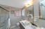 Renovated bath-vanity with double sinks and faucets, mirrors, marble tile tub surround, lighting, and dual flush toilet