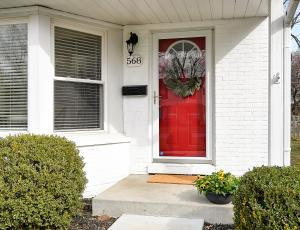 White painted brick with a cheery red door greets you at the end of a newly poured concrete walkway. Come in!