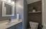 The first floor powder room with upgraded lighting, grey vanity and wood plank wall!