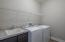 Fully equipped laundry room with a utility sink and cabinet.