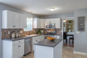 Kitchen offers white, raised panel cabinets, center island and stainless steel appliances.
