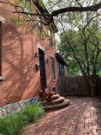 Light-filled, brick Italianate in heart of German Village, steps from shops, dining, fitness center, & park. Full renovation by top architectural firm preserved historic character and charm, w/exposed brick walls, original woodwork & floors. Open concept living/dining area w/wood burning fireplace, spacious updated kitchen w/ 6' X 3' granite island, breakfast nook, island seating, original walk-in pantry w/window, 2 walls of windows highlight professionally landscaped, fenced yard/brick patio. Staircase has been widened & leads to 2 spacious bedrooms, full bath w/8' double vanity & linen closet; walk-in closet with window can be used as office or nursery. Master bedroom includes 3 skylights w/custom shades. Interior has modern light fixtures & finishes to showcase this home's unique style!
