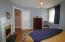 bedroom with double closet , decorative fireplace & hardwood flooring