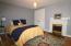 bedroom with decorative fireplace & hardwood flooring