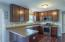 """The eat-in kitchen showcases 42"""" cabinets, stainless steel appliances (including a gas range), tile backsplash, pantry, breakfast bar and laminate flooring!"""