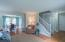 Living room and dining room are open to each other with hardwood flooring and white trim.