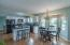 Bright and cheery eat-in kitchen with pantry, center island, white cabinets and backsplash, granite counters and hardwood flooring!