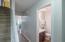 Half bath with hardwood flooring, granite counter, updated lighting and mirror.