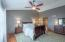 Vaulted owner's suite with hardwood flooring and ceiling fan/light combo.
