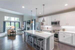 Large eat-in kitchen showcases upgraded white cabinets, granite countertops, tile backsplash, SS appliances, center island with pendant lighting, recessed lighting and a pantry!