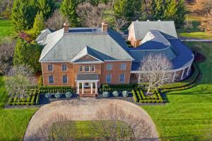 Stunning custom estate on wooded 1.38 acres in NACC/Fenway. Over 9,700 sq ft, this home provides ample space for entertaining and relaxation. Stately entrance with floating staircase & cathedral foyer opens to Great Room with walls of windows overlooking the multi-level brick terraces, mature trees & lush landscaping. Exquisite gourmet kitchen with oversized granite island. Amazing remodeled 1st floor owner's suite w/private patio. 5 fireplaces.Add'l 2nd floor owner's suite with sitting room.  Finished walkout lower level w/ bar, sauna, wine cellar, kitchen, fireplace, workout, media entertainment area & potential 6th BR w/full bath. Separate Carriage suite w/kitchen, full bath, LR w/fireplace and BR.  An exceptional home on outstanding lot. Home is in pristine condition.