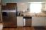 Kitchen offers stainless steel appliances, subway tile, and new flooring